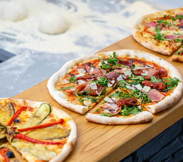 3 belles pizzas presentées sur un comptoir